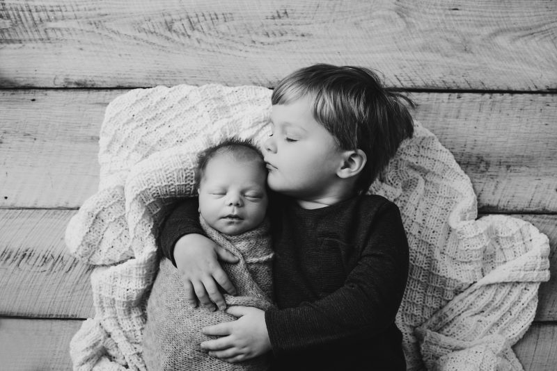 Black and white photo of big brother kissing on his baby brother