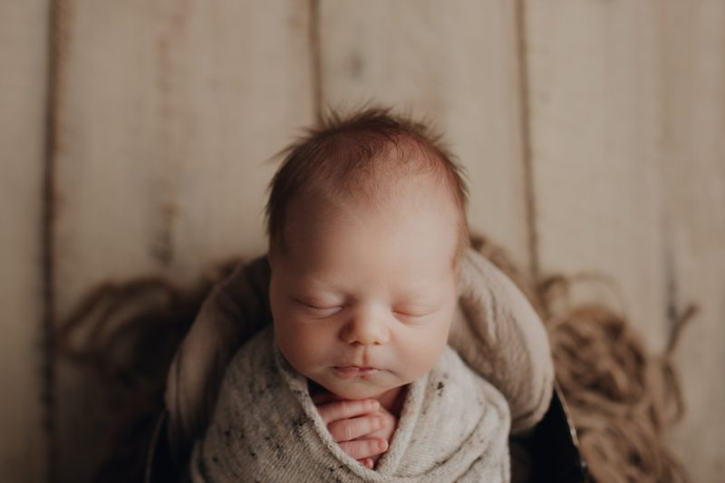 newborn baby boy in a bucket with white barnwood and wrapped in a cream wrap