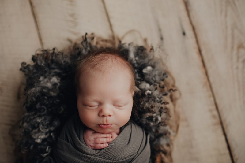 newborn baby laying on a grey fur with a white barnwood background