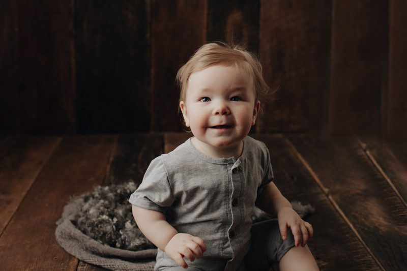 one year old getting photos sitting on brown barn wood