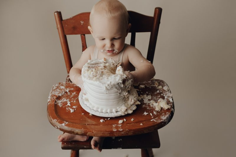 one year old baby boy digging into his first cake