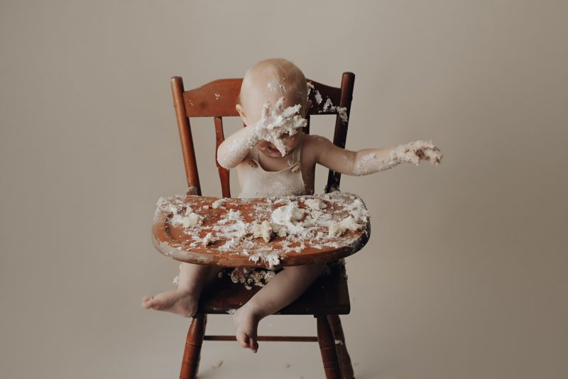 baby throwing cake off his high chair