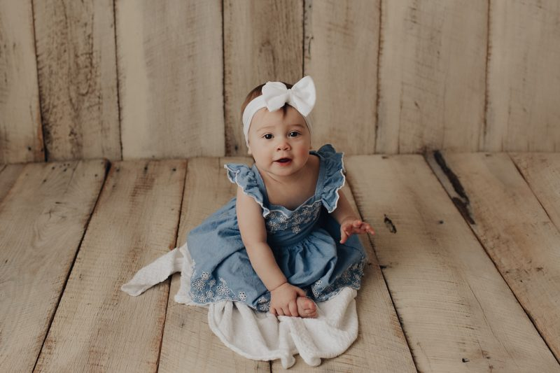 Sweet baby girl on a white washed backdrop getting her one year photos taken