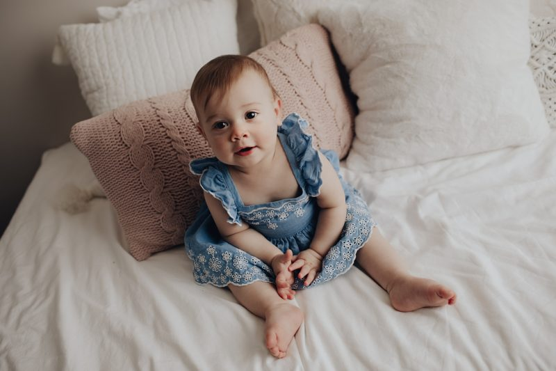 baby girl photos on a bed.