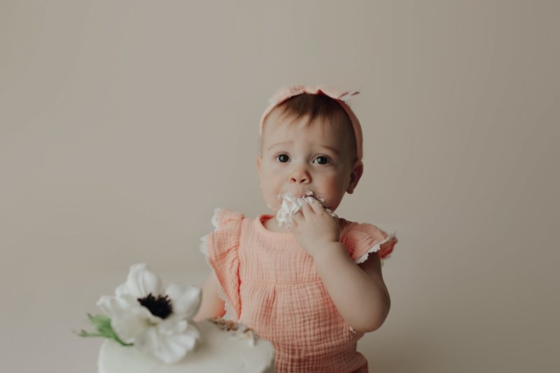 one year old enjoying cake for her one year session