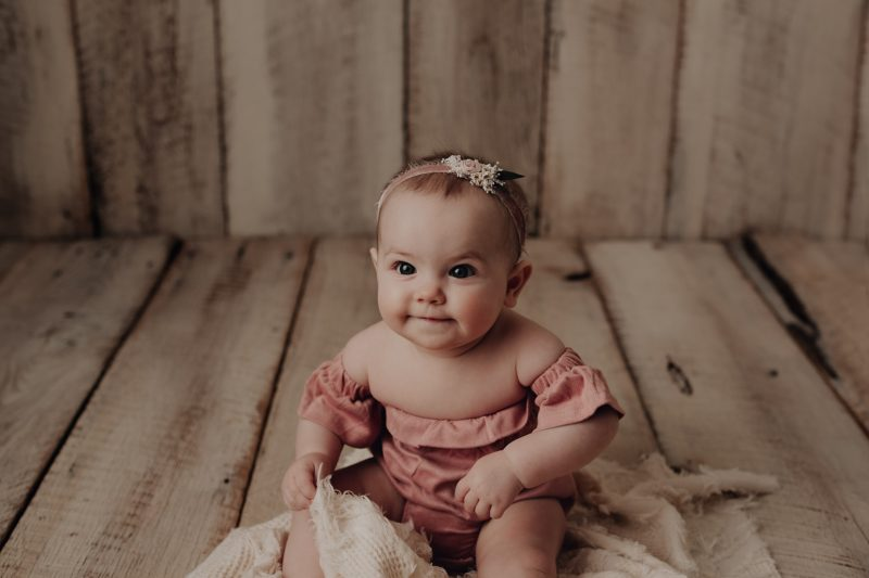 baby sitting on barnwood for her 6 month session
