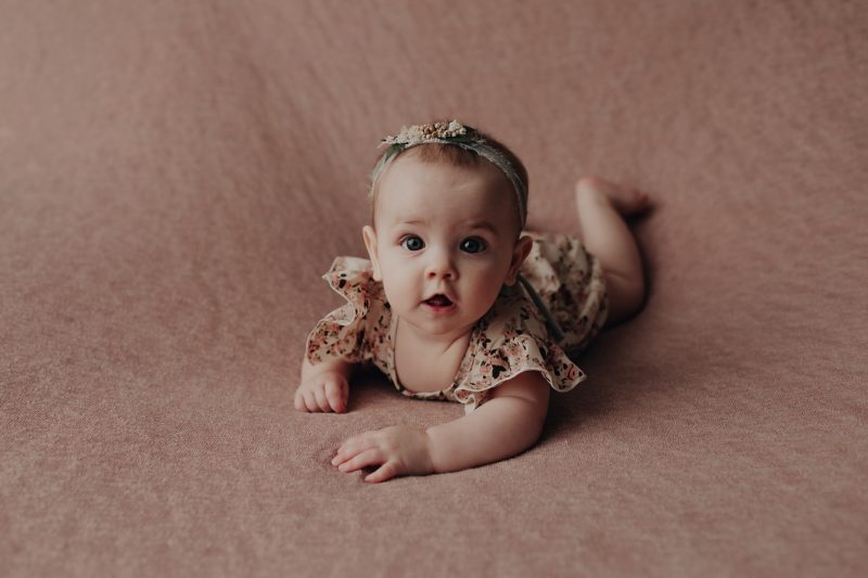 baby girl on her belly posing for 6 months photos