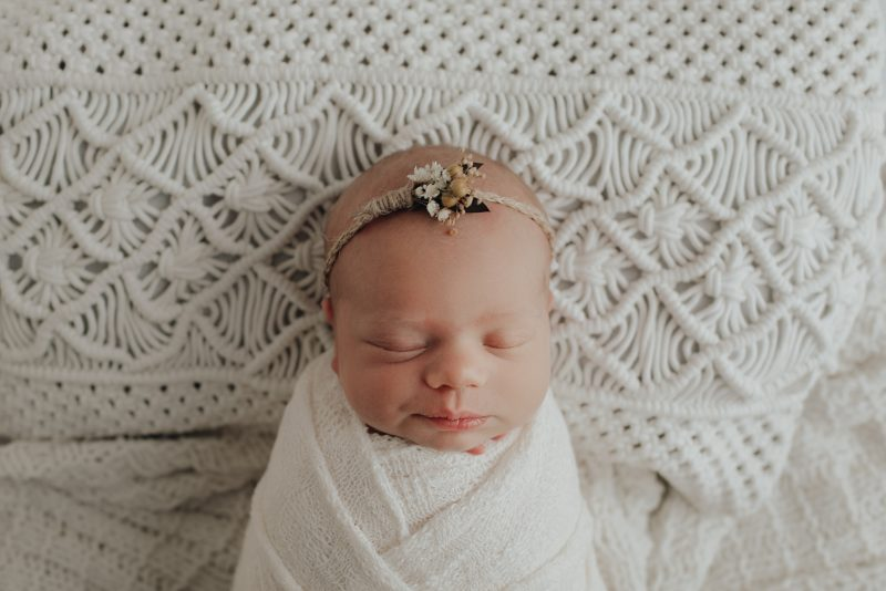 perfect newborn baby girl laying on a cream pillow with a cream wrap around her