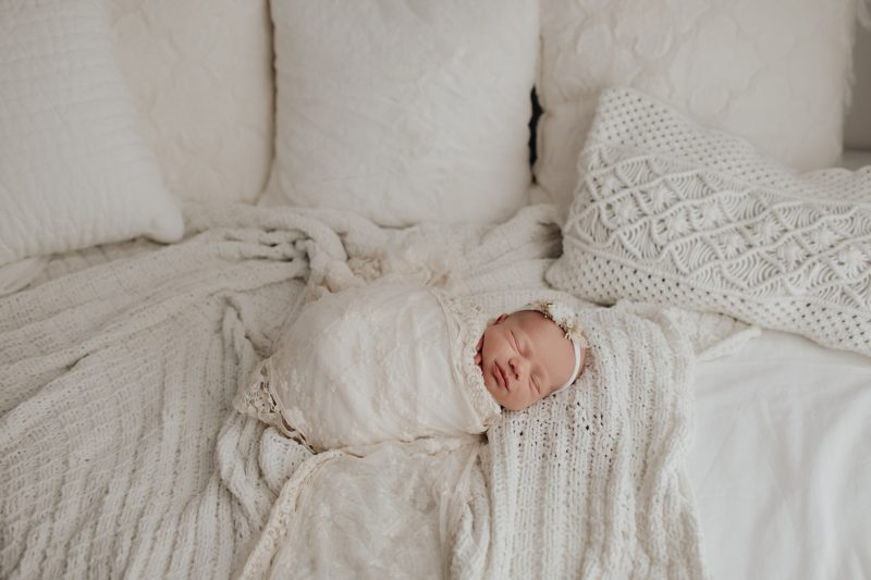 baby girl with a lace wrap over her posing for newborn photos