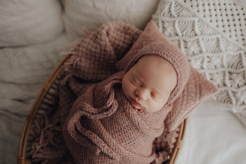 sweet baby wrapped in mauve wrap with bonnet