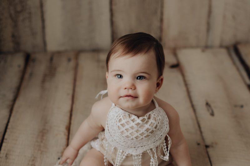 baby girl posing on white barnwood for her one year pictures