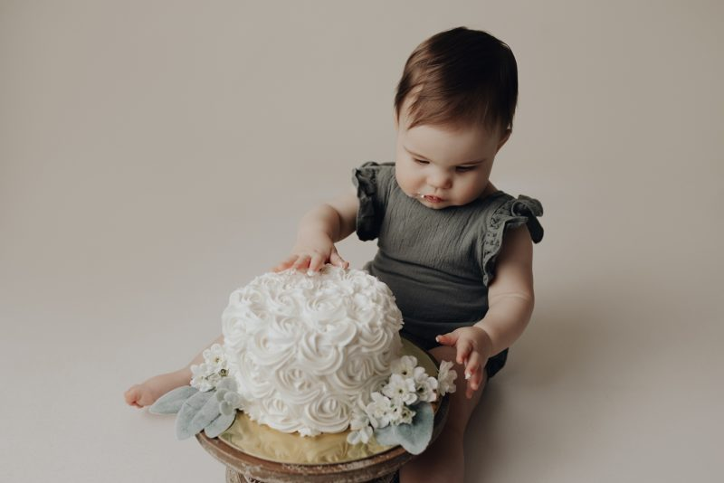 sweet girl eating cake for her one year cake smash photo session