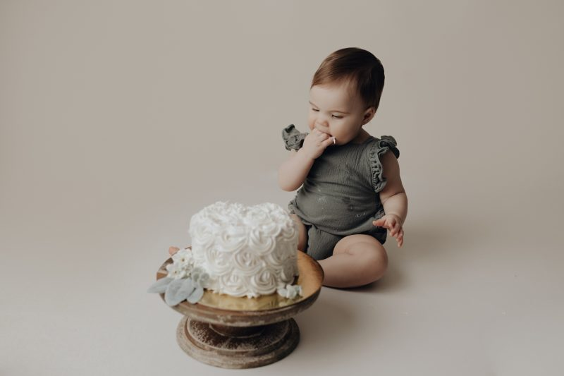 one year old eating cake for her photos