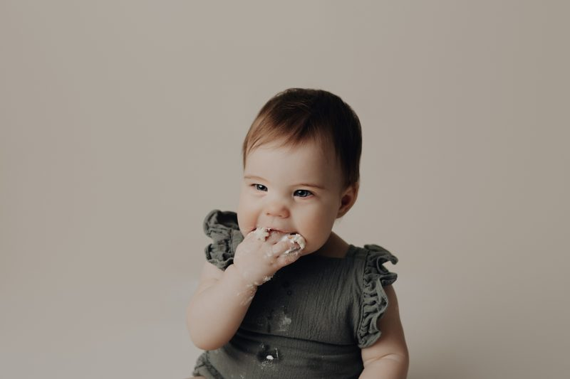sweet girl with a green romper eating cake for her birthday session