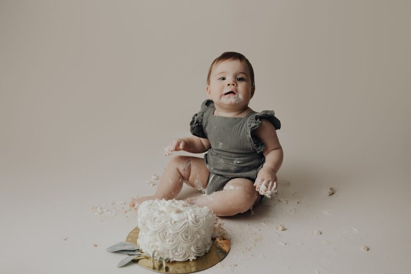 Sweet baby girl enjoying her cake for her one year session