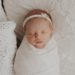 baby girl wrapped in a cream wrap laying on a pillow